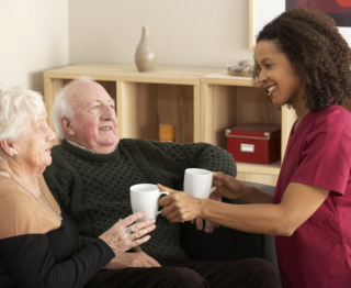 caregiver giving two cups of water to the elders
