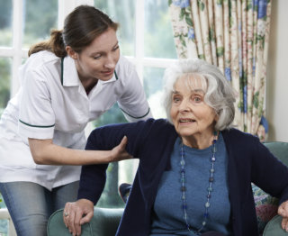 caregiver assisting elder to stand